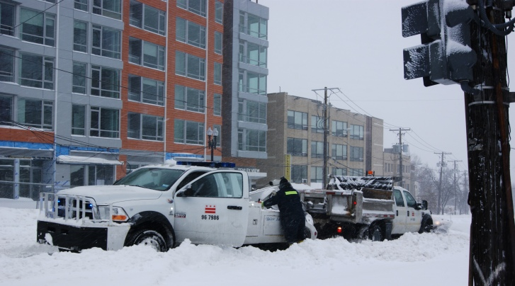 District snow plow getting a tow on Wisconsin Ave.